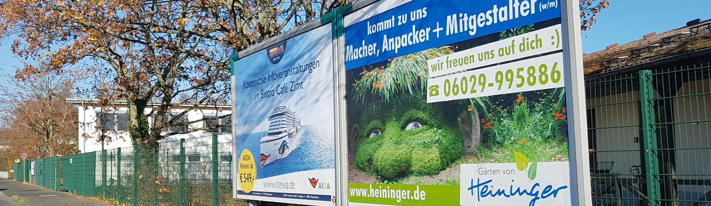 Unternehmen Heininger sucht auf Großplakat neue Mitarbeiter für den Gartenbau. Das Plakat ist witzig mit einem schelmisch in der Landschaft platziertem grün bewachsenen Kopf gestaltet. Text kommt zu uns, Macher, Anpacker und Mitgestalter